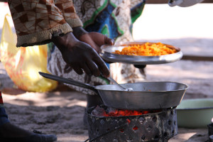 Woman adding pumpkin pulp to the pan to cook a dish of local fish, pumpkin and rape greens in the Barotse floodplain. (Bioversity International/ E.Hermanowicz)