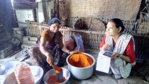 A woman sorting and storing ground spices while talking to an enumerator in Maharashtra, India (Picture credit: Vidya S.R. Vemireddy)